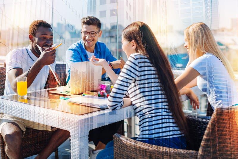 Amigos alegres que se divierten en el café imagen de archivo libre de regalías