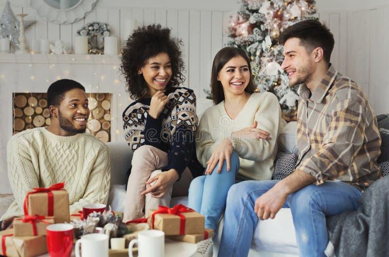 Amigos alegres que sentam-se e que falam perto da árvore do ano novo imagens de stock royalty free