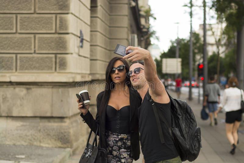 Amigos alegres que toman las fotos de ellos mismos en el teléfono elegante fotografía de archivo libre de regalías