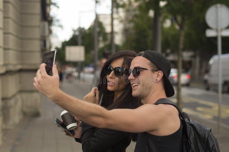Amigos alegres que toman las fotos de ellos mismos en el teléfono elegante foto de archivo libre de regalías