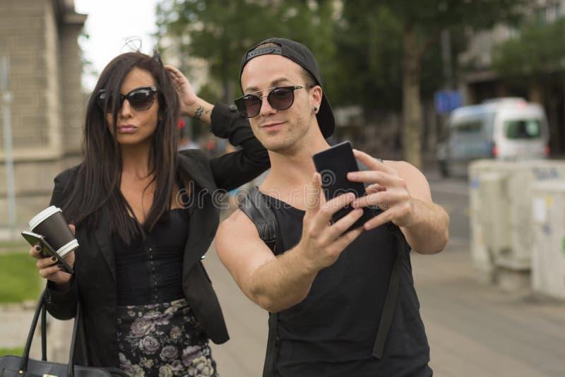 Amigos alegres que toman las fotos de ellos mismos en el teléfono elegante foto de archivo