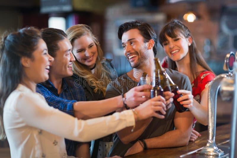 Amigos alegres que tuestan las botellas de cerveza foto de archivo