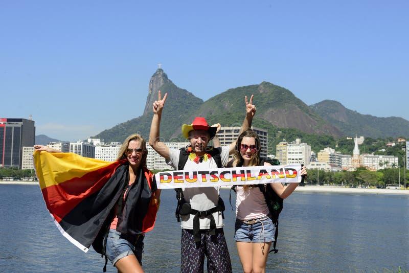 Amigos alemães que viajam em Rio de janeiro que guarda a bandeira alemão. fotos de stock royalty free