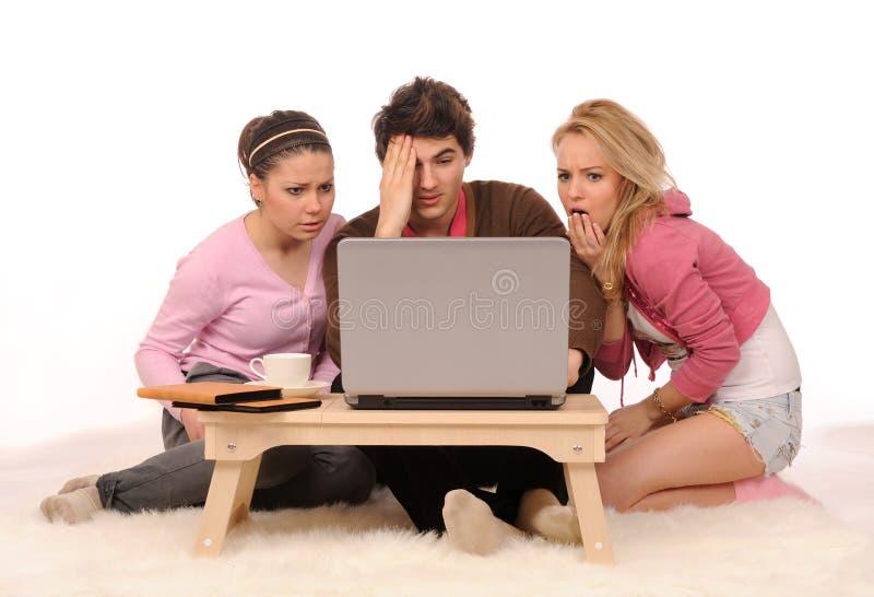 Amigos amedrontados com portátil. fotografia de stock