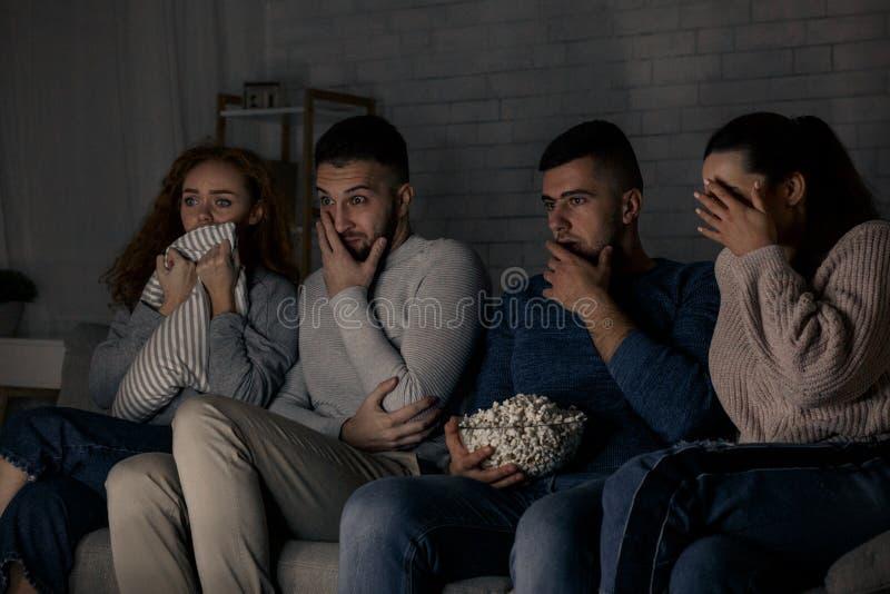 Amigos amedrontados que olham o filme e que comem a pipoca fotografia de stock royalty free