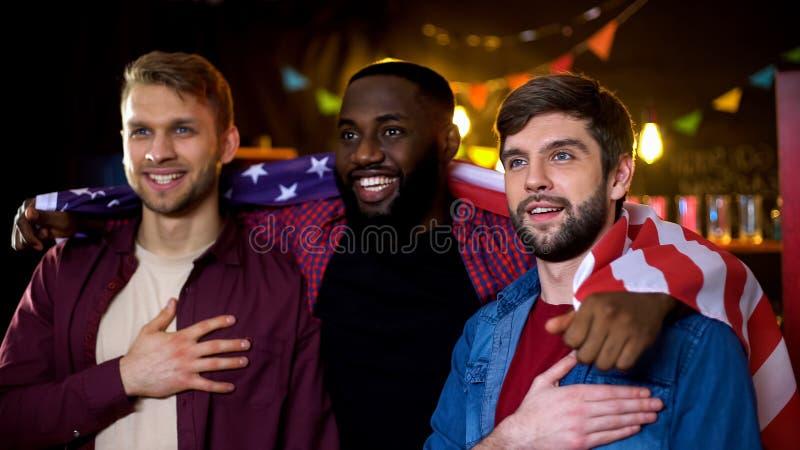 Amigos americanos envolvidos em resultados de eleição de observação da bandeira nacional na tevê fotografia de stock royalty free