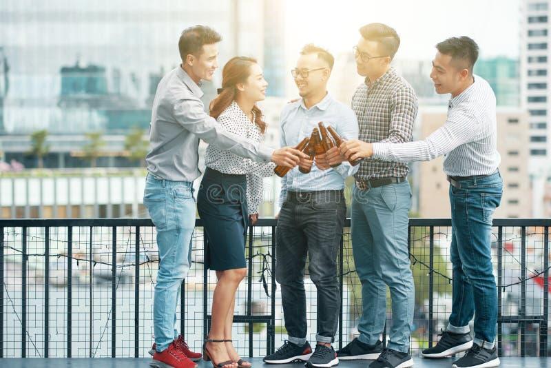 Amigos asiáticos alegres que tintinean con las botellas foto de archivo