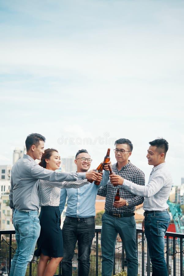 Amigos asiáticos contentos que tuestan con las botellas de cerveza imagenes de archivo