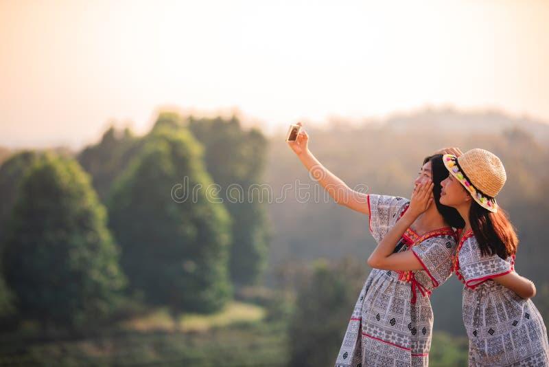 Amigos asiáticos da mulher que abraçam e para fazer junto a foto do selfie com telefone celular no por do sol foto de stock