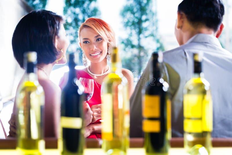 Amigos asiáticos que bebem o vinho na barra extravagante foto de stock