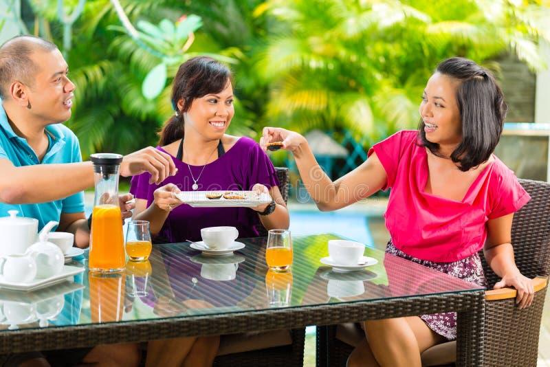 Amigos asiáticos que comen café en el pórtico casero fotos de archivo libres de regalías