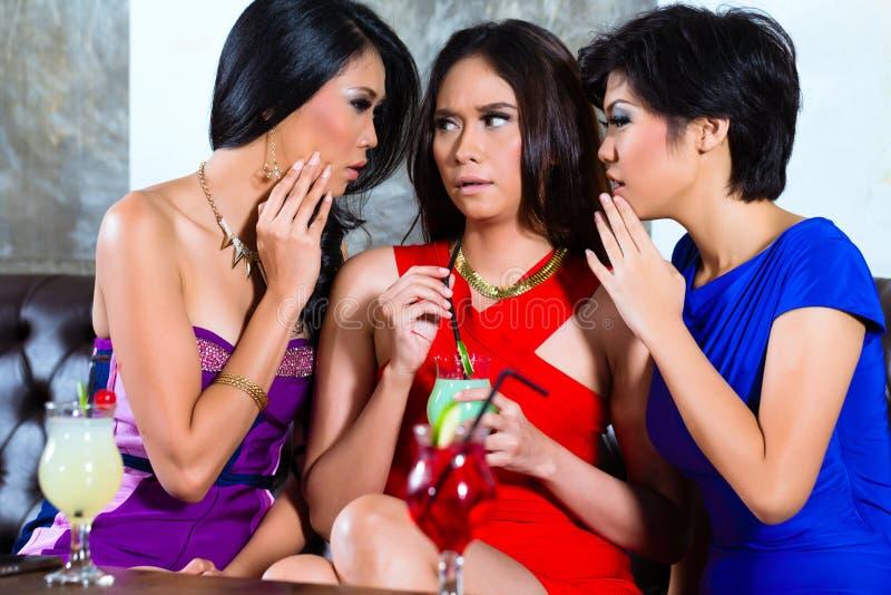 Amigos asiáticos que cotillean en club nocturno foto de archivo libre de regalías