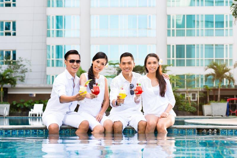 Amigos asiáticos que se sientan por la piscina del hotel fotos de archivo