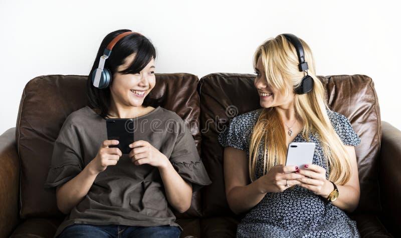 Amigos asiáticos y caucásicos felices de las mujeres que escuchan la música de la música junto y el concepto del ocio imágenes de archivo libres de regalías