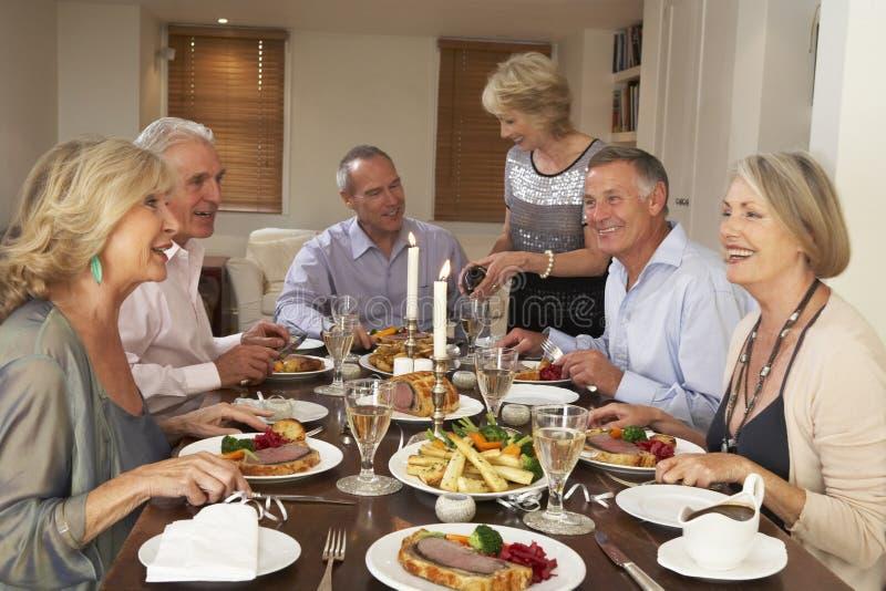 Amigos assentados na tabela para um partido de jantar fotografia de stock