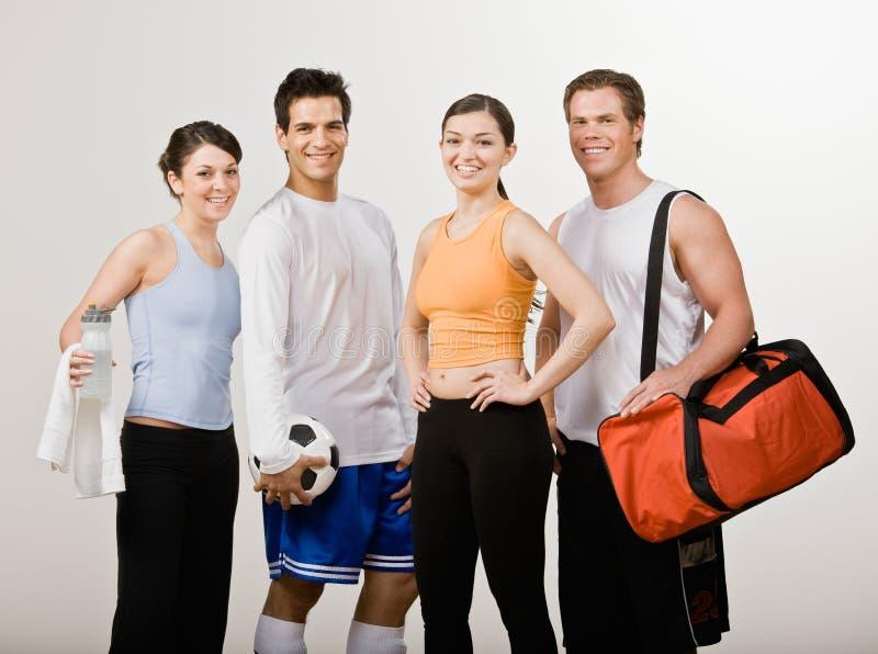 Amigos atléticos en ropa de deportes con el balón de fútbol imagen de archivo