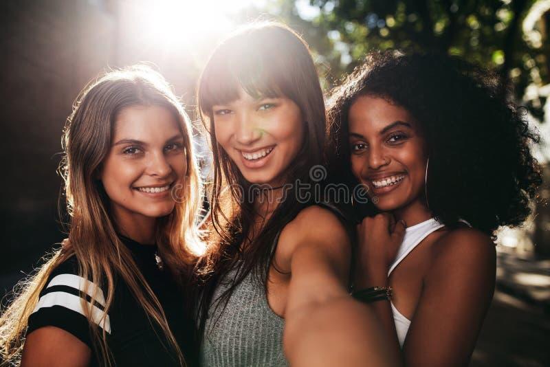 Amigos bonitos que estão junto na cidade e que tomam o selfie imagem de stock royalty free