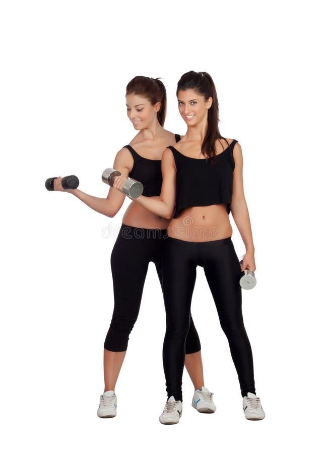 Amigos bonitos que treinam levantar peso foto de stock