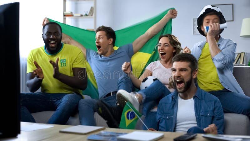 Amigos brasileiros felizes que olham o fósforo em casa comemorar o objetivo da equipa de futebol imagem de stock