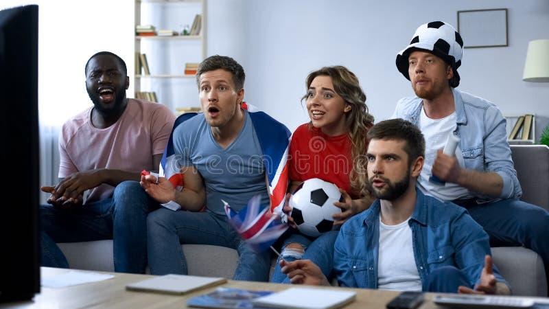 Amigos británicos que apoyan el equipo nacional, partido de fútbol de observación en la TV en casa fotos de archivo