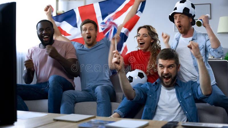 Amigos británicos que miran el partido de fútbol en la TV, meta que disfruta del equipo nacional fotografía de archivo