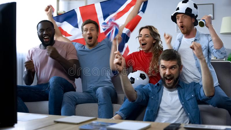 Amigos britânicos que olham o jogo de futebol na tevê, objetivo de júbilo da equipa nacional fotografia de stock