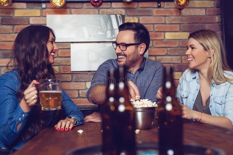 Amigos cercanos que disfrutan de la compañía de los eachothers, cerveza de consumición, snacking en un poco de palomitas foto de archivo