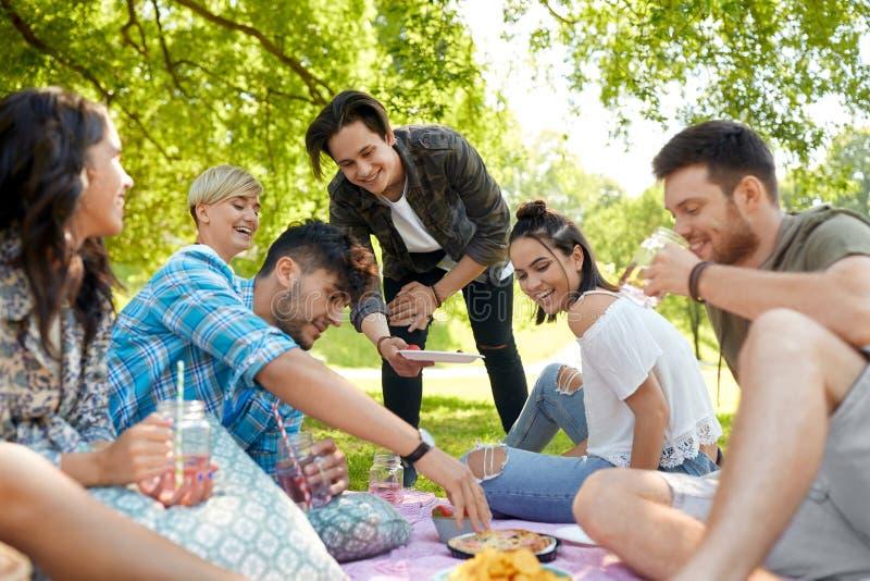 Amigos com bebidas e alimento no piquenique no parque imagem de stock