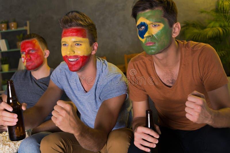Amigos com caras coloridas que olham o futebol imagens de stock