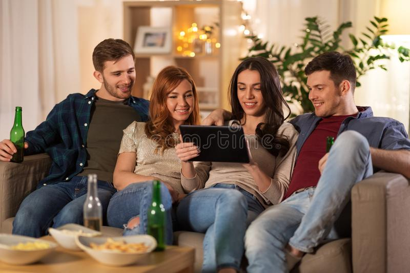 Amigos com cerveja bebendo do tablet pc em casa imagens de stock