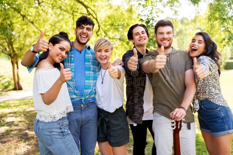 Amigos com a guitarra que mostra os polegares acima no parque imagem de stock royalty free