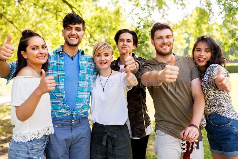 Amigos com a guitarra que mostra os polegares acima no parque fotos de stock royalty free