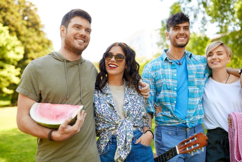 Amigos com a guitarra que vai tomar parte num piquenique no parque imagens de stock