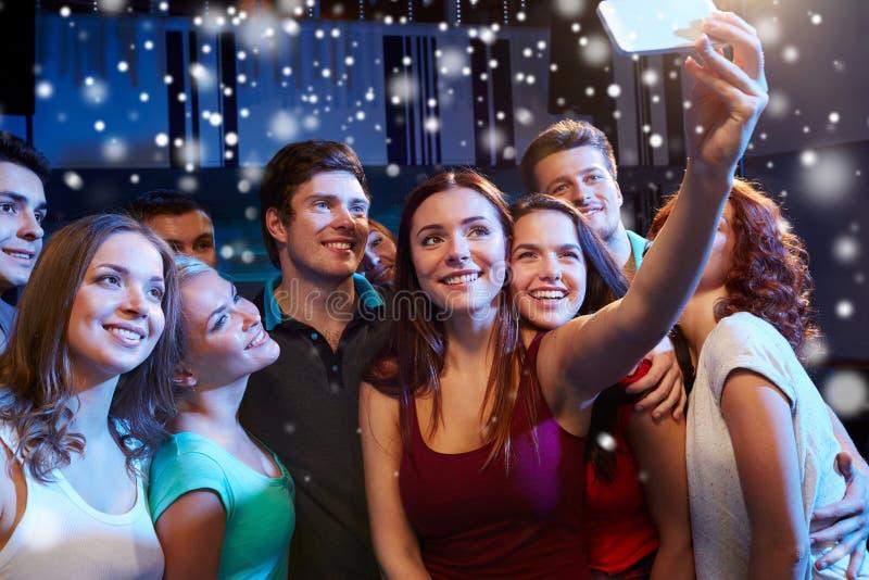 Amigos com o smartphone que toma o selfie no clube imagens de stock