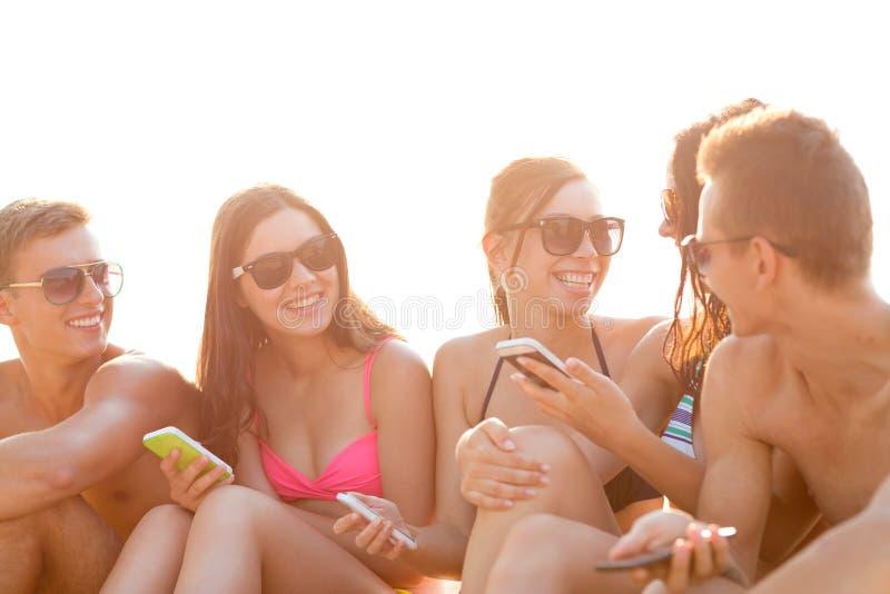 Amigos com os smartphones na praia fotografia de stock royalty free