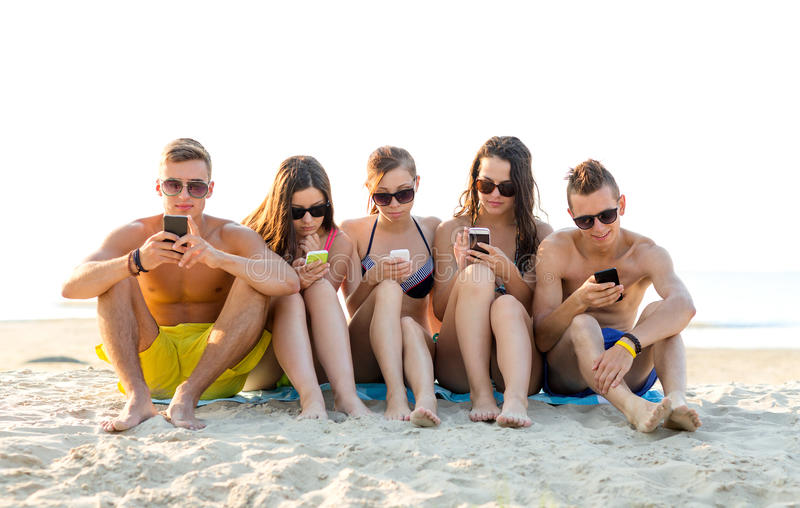 Amigos com os smartphones na praia imagens de stock