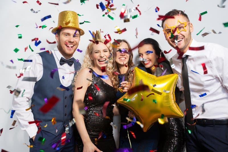 Amigos com riso dos suportes e dos confetes do partido imagem de stock royalty free