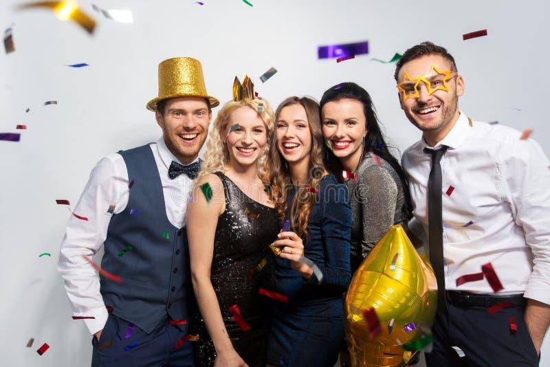 Amigos com riso dos suportes e dos confetes do partido imagens de stock royalty free