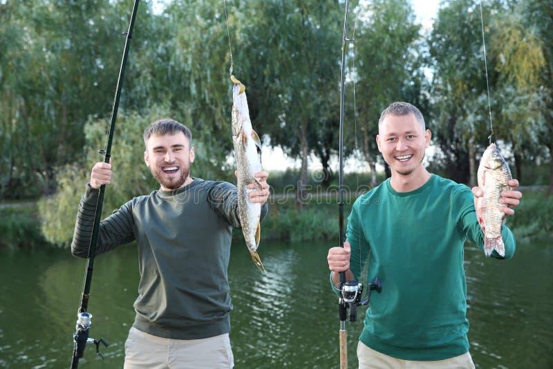 Amigos com varas de pesca e captura no beira-rio fotografia de stock royalty free