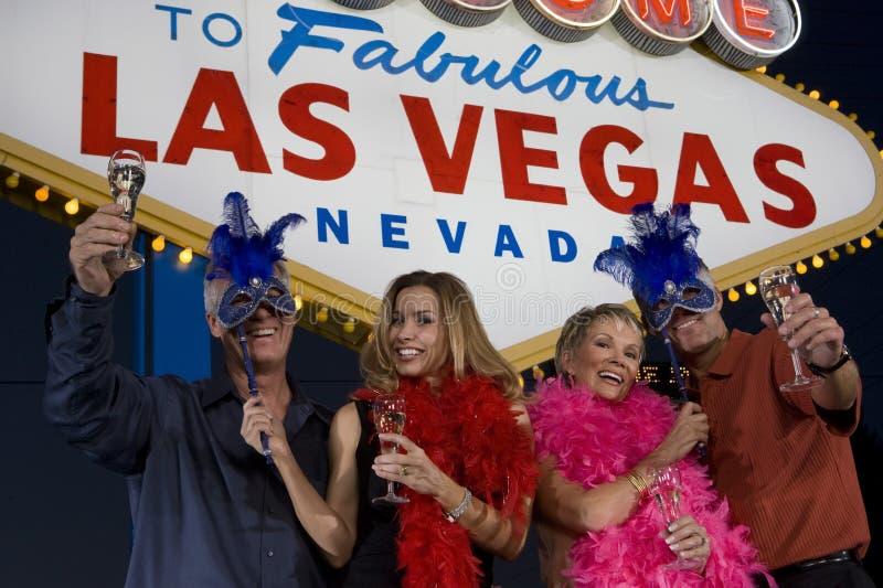 Amigos con Champagne And Carnival Masks foto de archivo libre de regalías