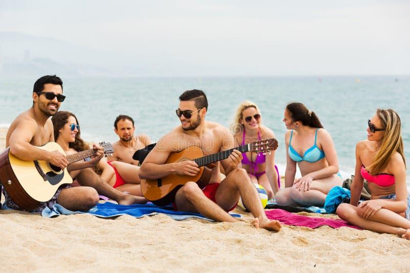 Amigos con la guitarra en la playa fotos de archivo