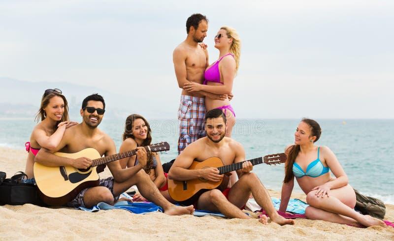 Amigos con la guitarra en la playa imágenes de archivo libres de regalías