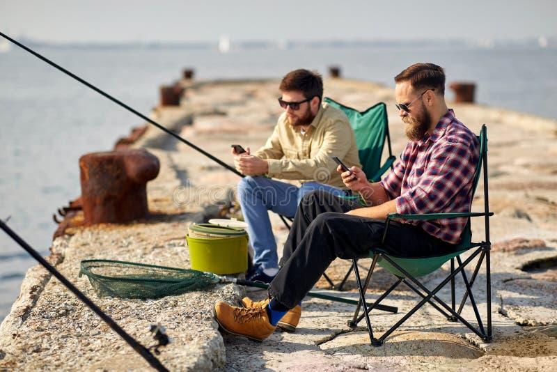 Amigos con los smartphones que pescan en el embarcadero en el mar foto de archivo