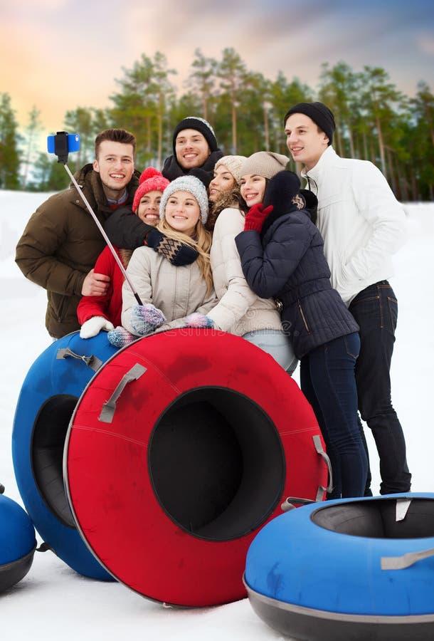 Amigos con los tubos de la nieve que toman el selfie en invierno foto de archivo