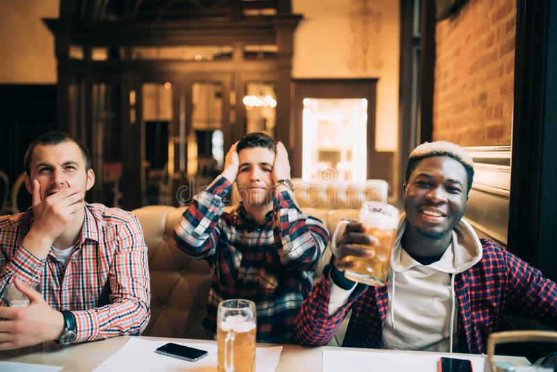 Amigos consideráveis novos alegres dos homens que têm o divertimento no jogo de observação do bar da cerveja em equipes diferente foto de stock royalty free