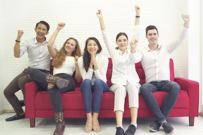 Amigos da comunidade do grupo de pessoas da diversidade que t?m o divertimento e o riso felizes junto, sentando-se no sof? vermel fotos de stock