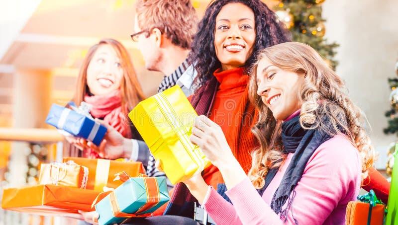 Amigos da diversidade com presentes de Natal e sacos que compram em m imagem de stock
