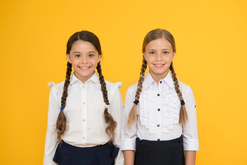 Amigos da escola crianças felizes no uniforme meninas no fundo amarelo Amizade e irmandade Melhores amigos imagem de stock royalty free