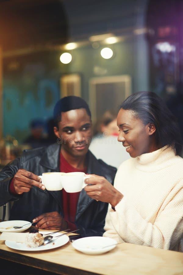 Amigos da faculdade do homem novo e da mulher que ligam copos ao se sentar junto no interior moderno do restaurante, imagem de stock
