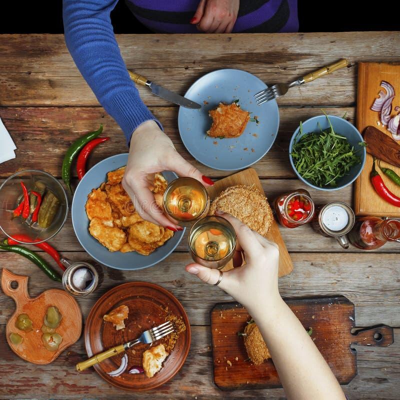 Amigos da reunião na tabela de jantar com petiscos e vinho americanos Acima dos vidros do brinde do vinho imagens de stock royalty free